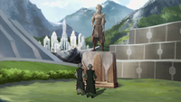 Lin and Su look at a statue of Toph