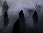 The hooded figures outside