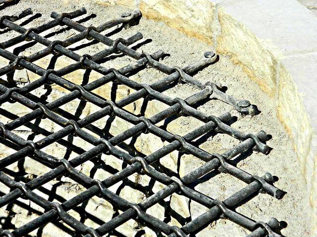Datei:Geschmiedetes Brunnengitter wechselseitige Kreuzlochung Detail Mauernägel.jpg