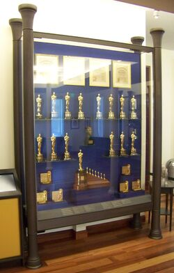 A large cabinet containing several golden statuettes and a few certificates.