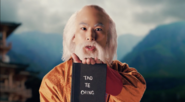 Lao Tzu holding the Tao Te Ching
