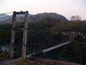Rustic, gray suspension bridge over a river