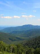 Green tree covered mountains turn blue as the progress toward the horizon.
