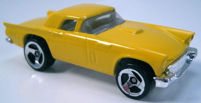 File:57 t bird yellow 3sp wheels chrome base clear glass.JPG