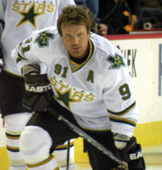 Hockey player in white Dallas Stars uniform, his helmet off. He leans forward and low, as if he were preparing to speed skate across the ice.
