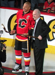 A man in full hockey uniform and another man in a dark suit hold a gold hockey stick together as they look toward an unseen photographer.