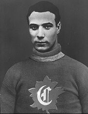 Half-length view of an ice hockey player in his late twenties. He has short black hair and a serious look. He is wearing a sweater with the letter C surrounded by a maple leaf on the chest.