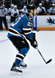 An ice hockey player, seen from the side, in a ready position. He is slightly crouched while standing on his skates and holds his stick in both hands. He wears a teal jersey with black trim, as well a black helmet.