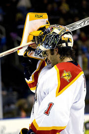 """An ice hockey goaltender removing his mask. He wears a white and orange jersey with the number """"1"""" on his elbow."""