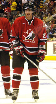 Hockey player in red Canada uniform. He stands on the ice, holding his stick on the ground, and looks to his right, lips slightly apart.