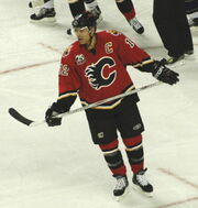 A hockey player in a red and black uniform with a stylized C logo on his chest skates across the ice.