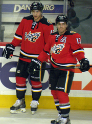"""Two hockey players in full uniform stand beside each other.  They are in matching red uniforms with black pants and black, white and yellow trim.  The jersey front says """"Calgary"""" in script with a small stylized """"C"""" logo."""