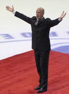 A bald man extends his hands to spectators at a hockey game. He is wearing black clothes and is standing on a red carpet.