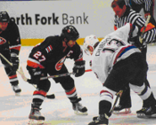 A hockey player taking a faceoff against his opponent. One player is wearing a blue, orange, and white jersey, and the other is wearing a white, blue, and red jersey.