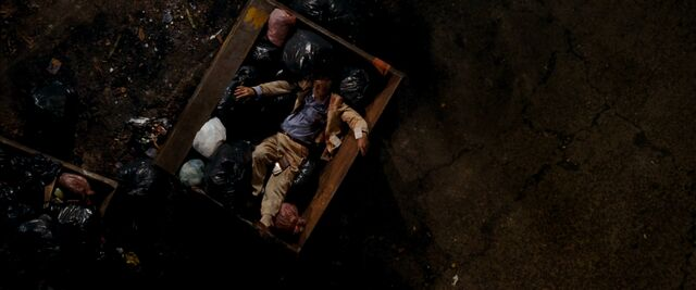 File:Quantum of Solace - Mathis thrown in a dumpster.jpg