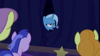 Trixie appears annoyed from behind the curtain S6E6