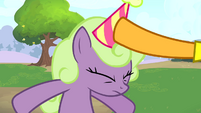 Cheese putting party hat onto a pony S4E12