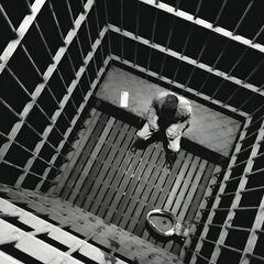 Alone in his cell.