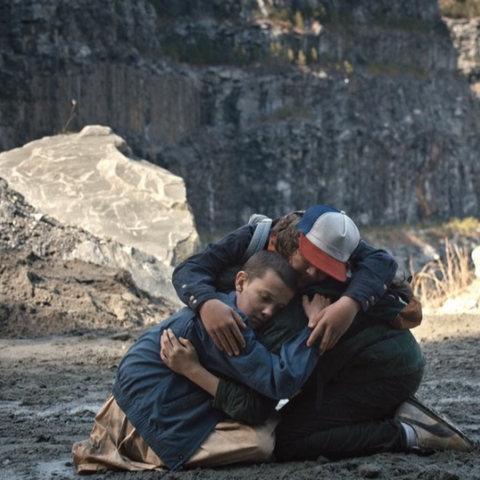 Dustin, Mike, and Eleven hug.