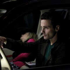 Logan driving a knocked out Caroline in the passenger seat.