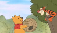 Winnie the Pooh hands over the paper beehive to Tigger