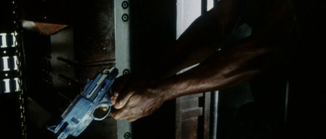File:Dr. Clauss holds pistol.jpg