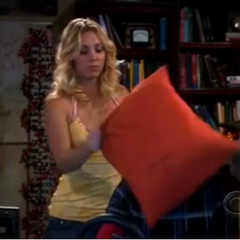 Penny simulating an airbag after Sheldon crashes his virtual car.