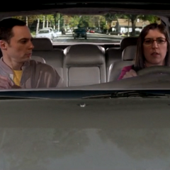 Amy driving Sheldon to work.