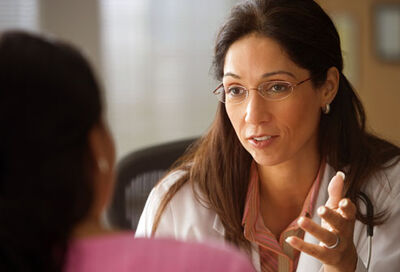 Getty rf photo of hispanic doctor talking to woman