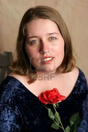 259744-a-beautiful-high-school-senior-posing-for-her-senior-portrait-with-a-red-rose