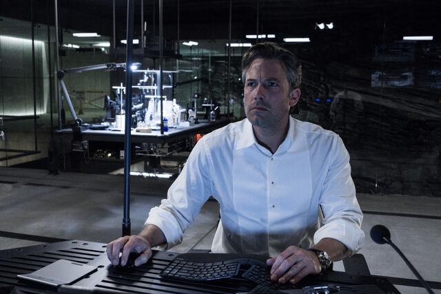 File:Bruce Wayne sitting at his computer.jpg