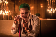 The Joker holds his cane and points