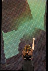 "A female teenager with long brown hair and a black dress stretches her fist upward. Only the teen's back is visible, as she is facing a large screen behind her. On the screen is the silhouette of a male teen caressing the face of a shorter female teenager.Cyrus sings ""When I Look at You"" during her Wonder World Tour while facing a screen playing a film clip of Will and Ronnie."