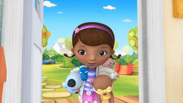 File:Doc with stuffed animals in her hands.jpg