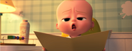 Boss Baby talking to Tim while holding book