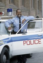 Carl Winslow (smiling) outside the cop car