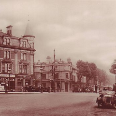 The more quaint and green section of the Blithebeth High Street. Due to the road's considerable width, pavements were broadened to make space for trees and a small central pavement (containing traffic lights and flower beds). The photo was taken in 1938, and all of the buildings still remain.