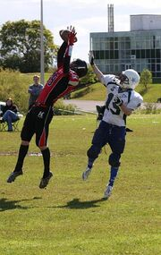 Two football players, an offensive receiver and a defensive cornerback, both reach for a thrown football. The cornerback is in front of the receiver with the ball almost secured in his hands.