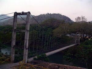 Rustic, gray suspension bridge over a river