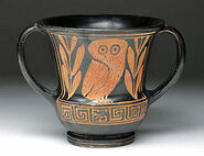 Athens, Greece, Ca 2nd quarter 5th century BCE. Super rare and wonderful pottery kantharos. Decorated in red-figure technique with owl looking forward standing between two laurel sprigs, Greek key along base