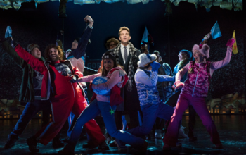 Phil surrounded by townsfolk in the Broadway production