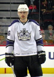 An ice hockey player standing facing towards the camera. He is wearing a white helmet, and a white, black, and purple uniform with a large crown on his chest.