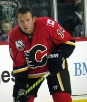 "Hockey player in red uniform with a big ""C"" in the middle. He stares, grim faced, directly at the camera, his stick pointing downward"