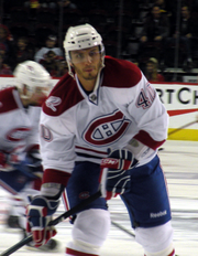 A Caucasian ice hockey player in his mid-twenties. He holds his hockey stick in a ready position while looking forward. He wears a white, visored helmet and a white jersey with red trim.