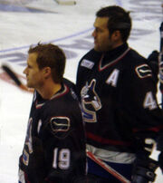 Two ice hockey players are standing next to one another and looking forward. Neither are wearing their helmets. They wear black jerseys.