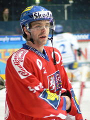 An ice hockey player standing, looking to the right of the camera. He is wearing a blue helmet and a red uniform.