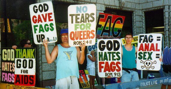 "Photo of a member of the Westboro Baptist Church holding signs that say, ""God hates fags"" and ""No tears for queers."""