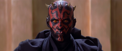 Heads and shoulders shot of a man wearing black robes. He is bald and has horns on his head, his face is covered in black and red tattoos, and his eyes are yellow.