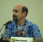 "A Caucasian bald man with a black beard looks to the left while speaking into a microphone. A plaque with the Comic-Con logo on the table reads ""Mike Stemmle""."