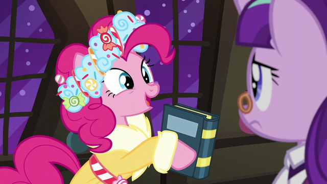 File:Spirit of HW Presents holding a book S6E8.png
